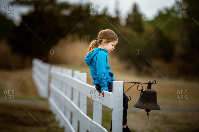 Girl sitting on white picket fence