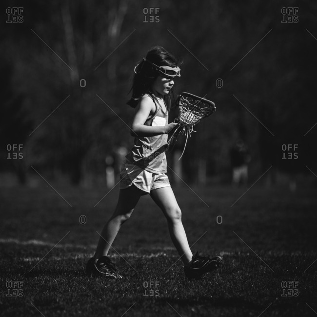 Girl playing lacrosse on field