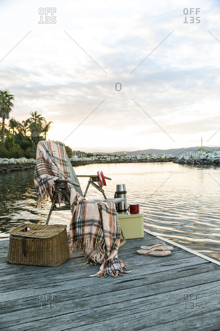 Fishing creel and folding chair with a blanket at the edge of a wooden dock
