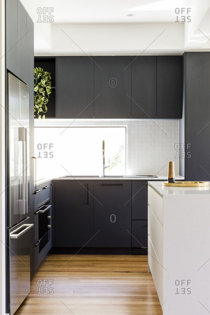 Modern kitchen with hardwood floors and black cabinetry