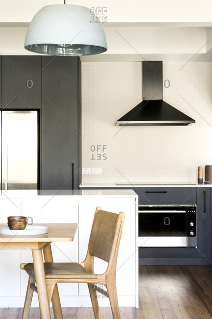 Modern kitchen with wooden table in dining area and built-in oven