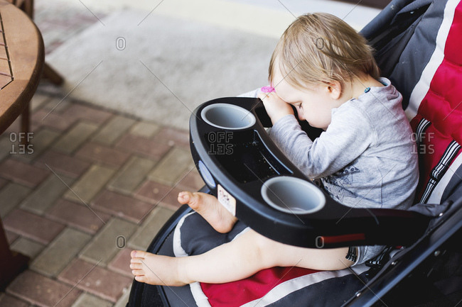 Baby asleep with his head down on stroller
