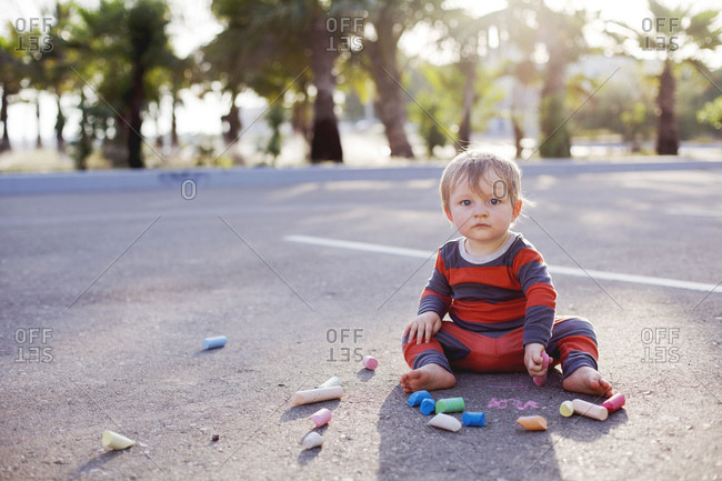 Toddler boy in pajamas drawing on sidewalk with chalk