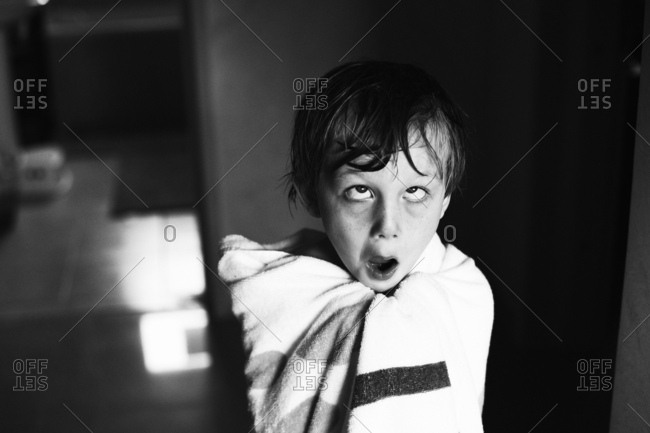 Child making a funny face while wrapped in towel