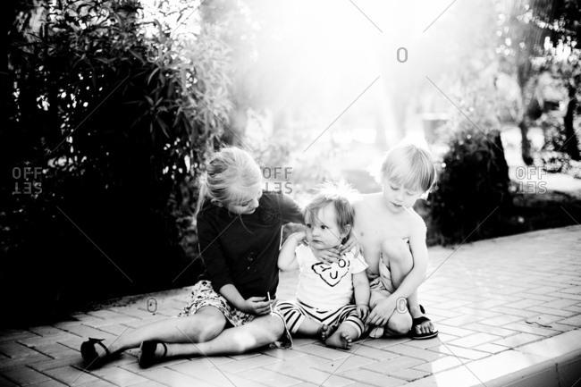 Three young children sitting on sidewalk