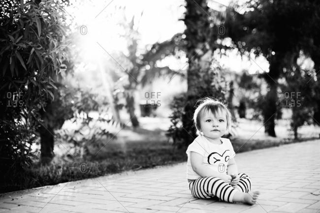 Portrait of toddler sitting on sidewalk