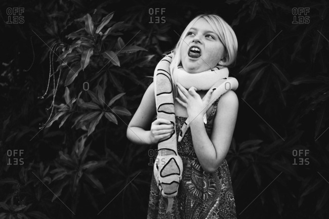 Girl pretending like she is being strangled by a boa constrictor