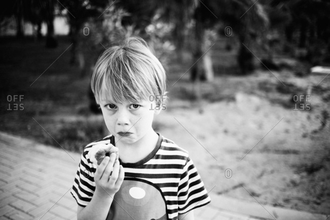 Boy with a sad face eating an apple