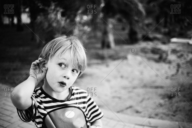 Expressive young boy pretending to listen to sound