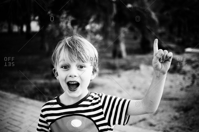 Excited young boy pointing his finger in the air