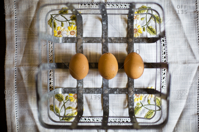 Overhead view of three brown eggs in metal basket on vintage cloth