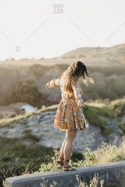 A girl balancing on a walkway in a sundress