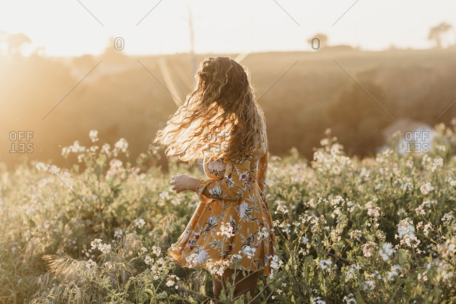 A girl with curly hair spinning in a flower field