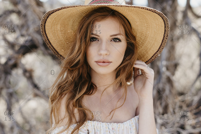 A portrait of a redhead girl in a straw hat