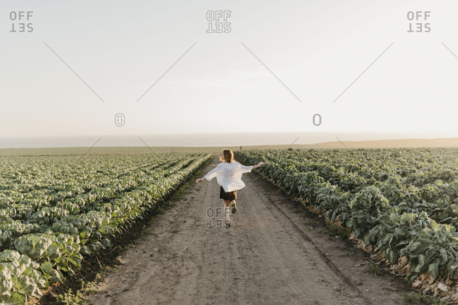 A Girl Runs Through Farm Field