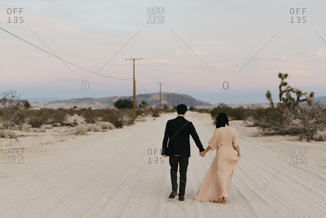 A couple walking down a desert road