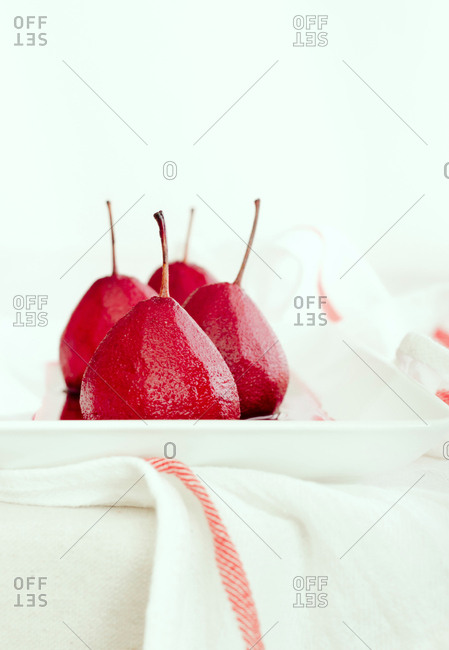 Scarlet poached pears on a white plate