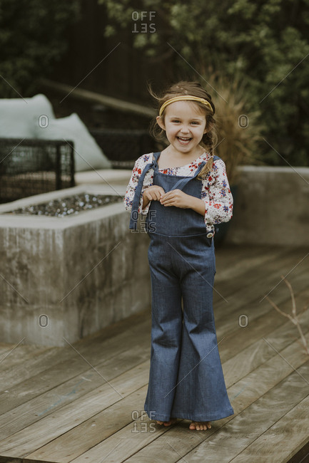 Little girl in bell-bottom overalls standing on a patio