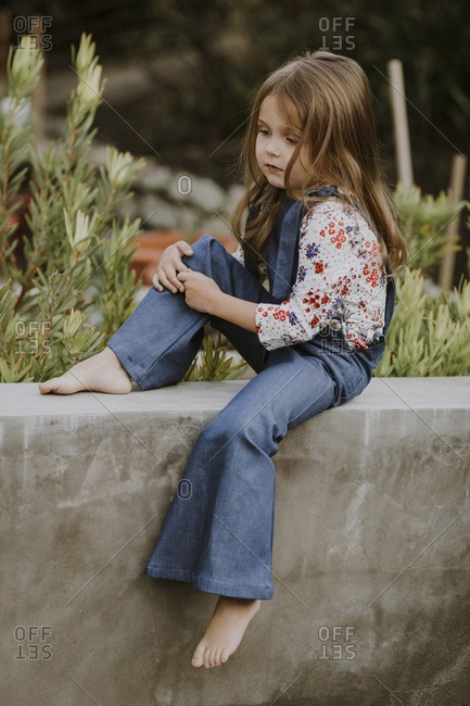 Sad little girl in bell-bottom overalls sitting on a cement wall