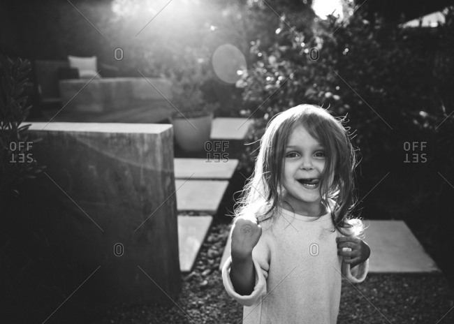 Little girl standing in a garden making a silly face