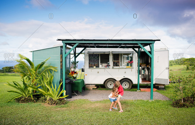 Brother and sister standing in front of a food truck hugging