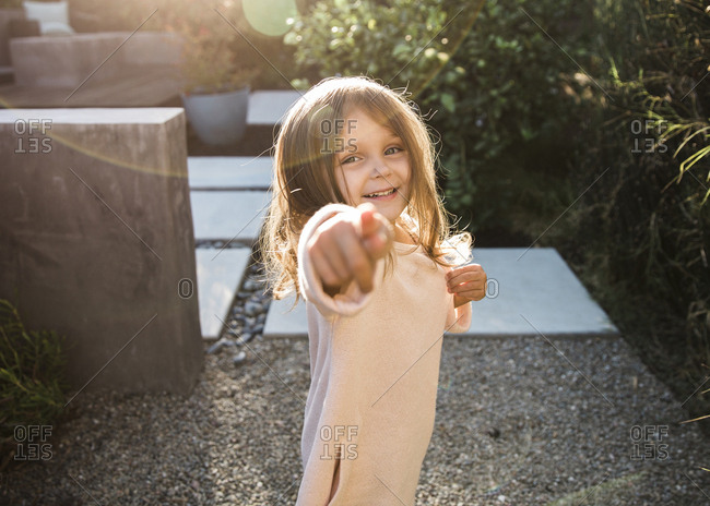 Little girl standing in a garden pointing at the camera