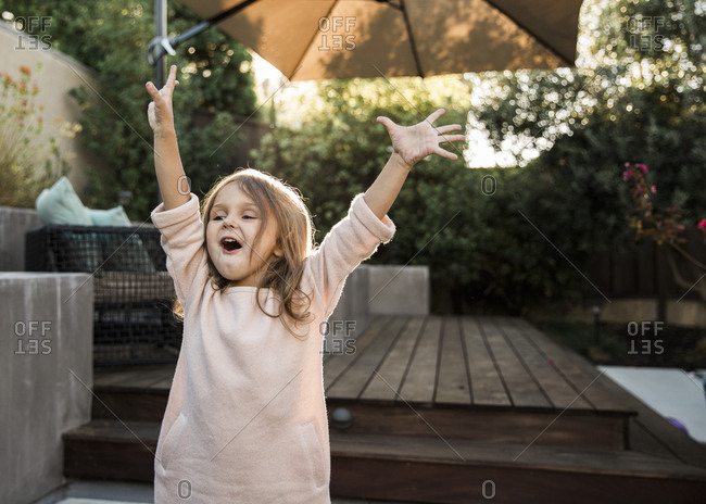 Little girl standing on a patio raising her arms in the air