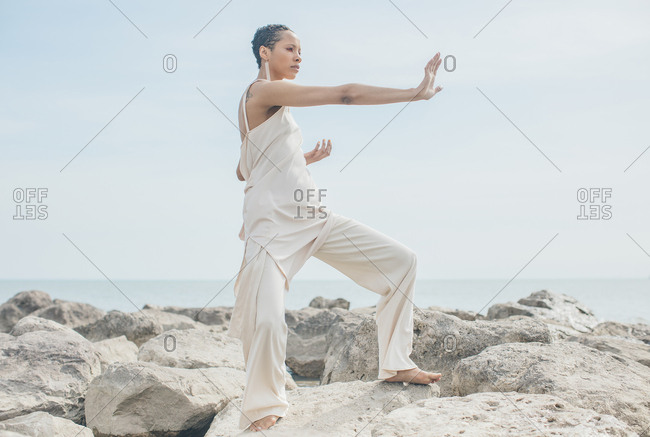 Woman standing in a martial arts pose on rocks