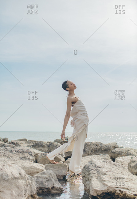 Young woman on rocks leaning against the breeze
