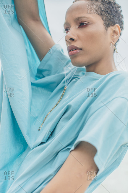 Stylish young woman in holding blue fabric from her shirt above her head
