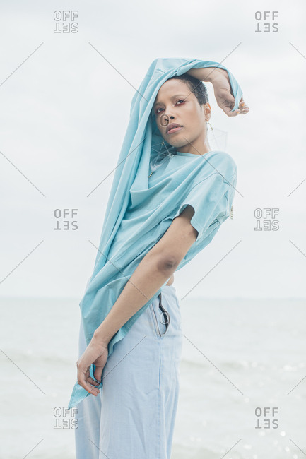 Stylish young woman in holding blue fabric from her shirt above her head beside a lake