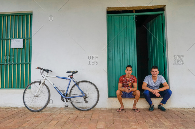 Vinales, Cuba - March 4, 2016: Two young men sitting in a doorway beside a bicycle
