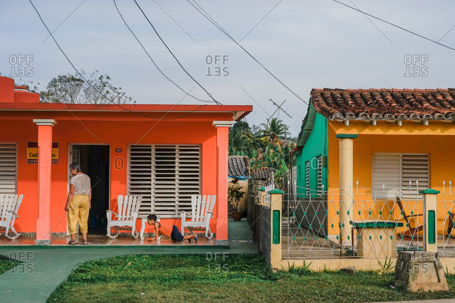 Vinales, Cuba - March 4, 2016: People on porches of colorful houses in a neighborhood