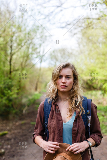 Backpacker standing on a forest trail holding her hat