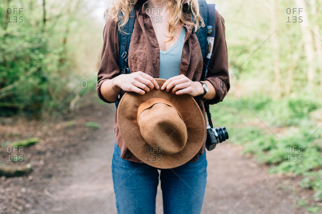 Hands of a backpacker standing on a trail holding her hat