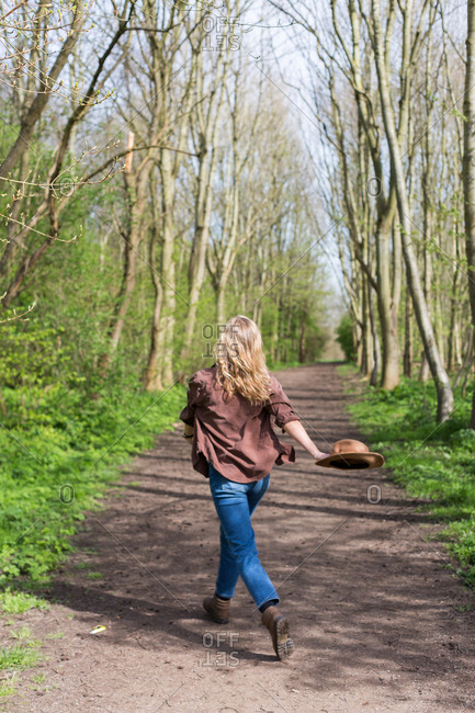 Young woman walking on a trail in the forest holding a hat