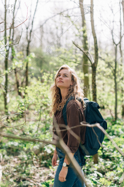 Young woman backpacking in a forest looking at the trees