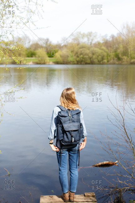 Backpacker standing in a small pier looking at a pond