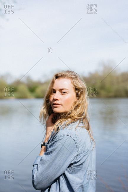 Young woman standing at the edge of a lake touching her hair