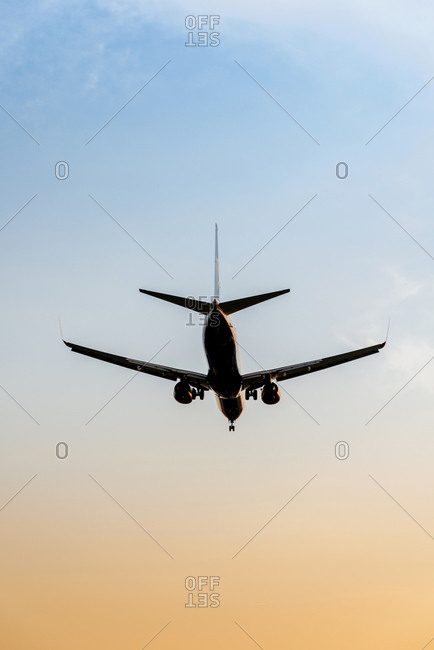Airplane flying in a sky at sunset