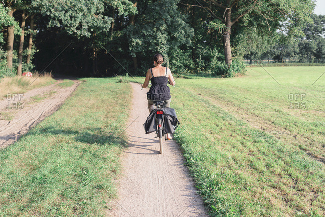 Female tourist cycling on sand path in dutch rural summer landscape