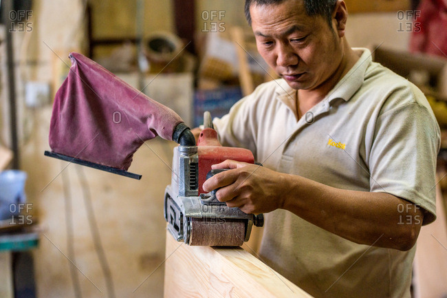 Kunming, China - July 6, 2015: Man operating a belt sander