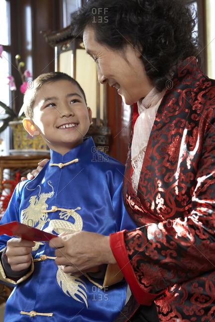 Traditionally Dressed Grandmother Handing Her Grandson An Envelope