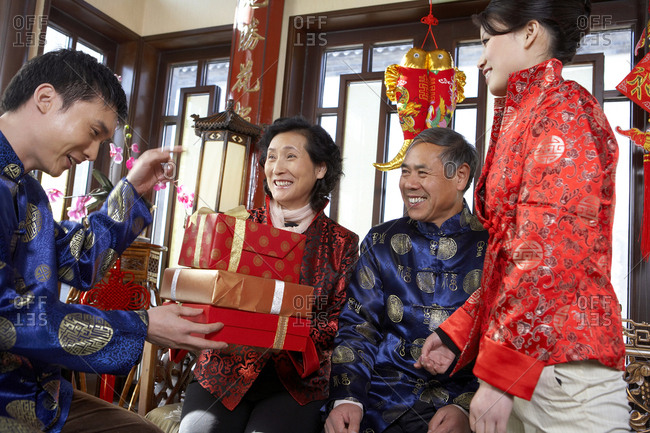 Traditionally Dressed Couple Receiving Gifts From Adult Son