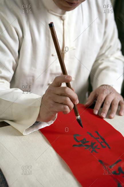 High Angle View Of Man Doing Calligraphy