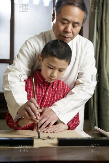 Man Teaching His Grandson The Art Of Calligraphy