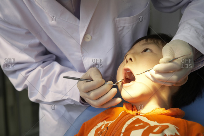 Dentist Examining Boy's Teeth