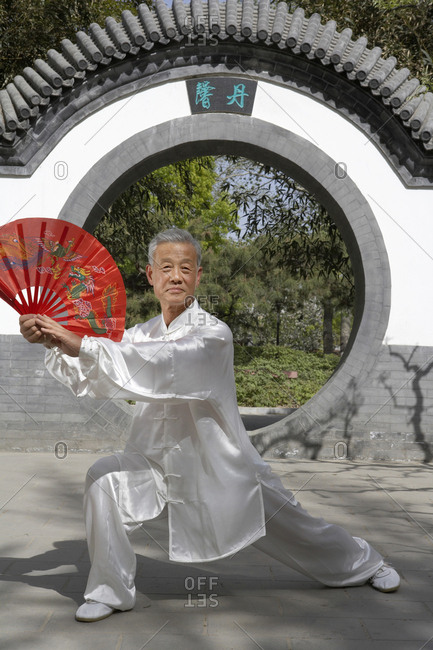 Elderly Man Practicing Martial Arts With A Fan