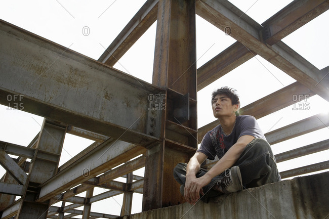 Young Man Sitting On A Beam In A Construction Site