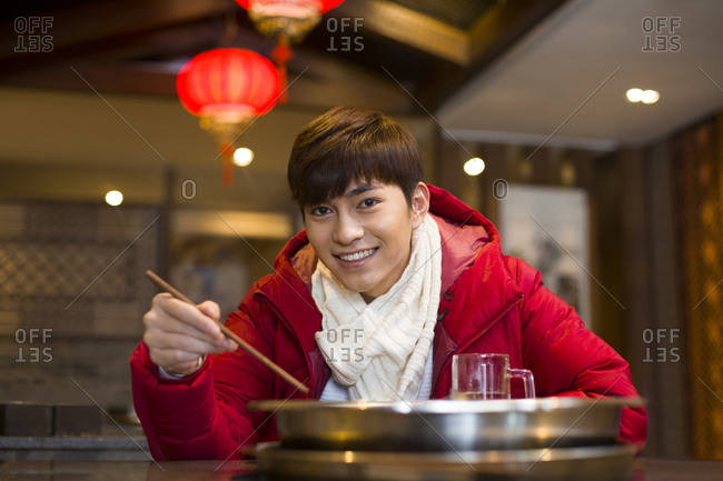 Young man having dinner in hotpot restaurant